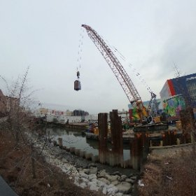 The EPA pilot project continues in the Fourth Street basin of the Gowanus Canal. Even it creates ludicrous scenes as what looks like the Tardus from Doctor Who hangs from the cable of the crane flying through the air.