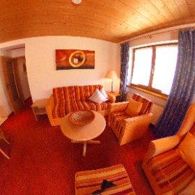 Zweiraumferienwohnung Nr. 11 (50 qm groß) , hier das Wohnzimmer mit eigener Terrasse und Gartenbestuhlung und Liege.