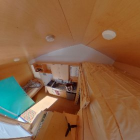 The larger of the two tiny home models has a second full-sized bed in a loft above the bathroom.